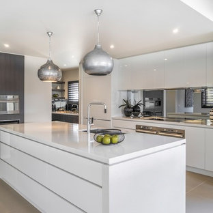 Contemporary kitchen in Melbourne with an undermount sink, flat-panel cabinets, white cabinets, mirror splashback, stainless steel appliances, an island, grey floor and white benchtop.