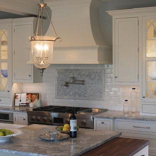 Mittelgroße Klassische Wohnküche in L-Form mit Kassettenfronten, gelben Schränken, Quarzit-Arbeitsplatte, Küchenrückwand in Weiß, Rückwand aus Marmor, Kücheninsel und blauer Arbeitsplatte in New York
