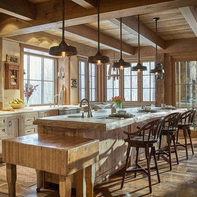 Mountain style medium tone wood floor and brown floor eat-in kitchen photo in Burlington with a farmhouse sink, shaker cabinets, wood countertops, gray backsplash, stone tile backsplash, stainless steel appliances, an island, beige countertops and light wood cabinets