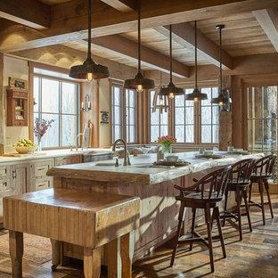 Foto på ett rustikt beige kök, med en rustik diskho, skåp i shakerstil, träbänkskiva, grått stänkskydd, stänkskydd i stenkakel, rostfria vitvaror, mellanmörkt trägolv, en köksö, brunt golv och skåp i ljust trä