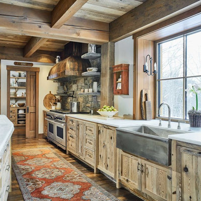 Kitchen - rustic galley medium tone wood floor and brown floor kitchen idea in Burlington with a farmhouse sink, shaker cabinets, light wood cabinets, gray backsplash, stone tile backsplash, stainless steel appliances, an island and white countertops