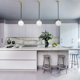 Large contemporary l-shaped kitchen in London with flat-panel cabinets, composite countertops, white splashback, stone slab splashback, an island, white worktops, white cabinets, white appliances and grey floors.