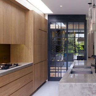 This is an example of a contemporary kitchen in London with a submerged sink, flat-panel cabinets, medium wood cabinets, metallic splashback and metal splashback.