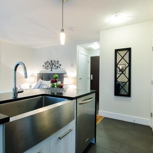Small contemporary single-wall open plan kitchen in Vancouver with shaker cabinets, white cabinets, with island, terrazzo benchtops, a farmhouse sink, stainless steel appliances and porcelain floors.