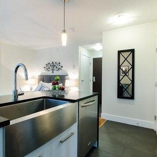 Modelo de cocina lineal, contemporánea, pequeña, abierta, con armarios estilo shaker, puertas de armario blancas, una isla, encimera de terrazo, fregadero sobremueble, electrodomésticos de acero inoxidable y suelo de baldosas de porcelana