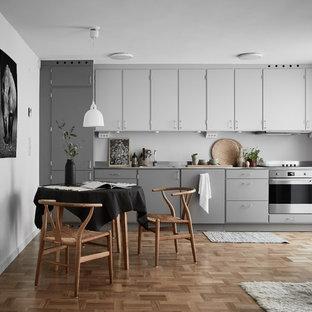 Inspiration för ett minimalistiskt linjärt kök och matrum, med släta luckor, grå skåp, grått stänkskydd, rostfria vitvaror, mellanmörkt trägolv och brunt golv