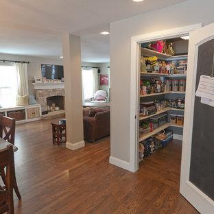 Bild på ett stort vintage kök, med en undermonterad diskho, luckor med upphöjd panel, vita skåp, granitbänkskiva, beige stänkskydd, stänkskydd i cementkakel, rostfria vitvaror, mellanmörkt trägolv och en köksö