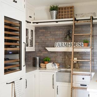 Immagine di una grande cucina a L country con lavello stile country, ante bianche, paraspruzzi multicolore, paraspruzzi in mattoni, elettrodomestici in acciaio inossidabile, isola e top bianco