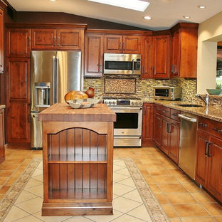 Mid-sized southwestern open concept kitchen inspiration - Mid-sized southwest u-shaped ceramic tile open concept kitchen photo in Phoenix with an undermount sink, stainless steel appliances, an island, recessed-panel cabinets, dark wood cabinets, granite countertops, beige backsplash and matchstick tile backsplash