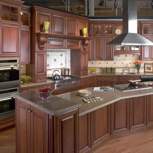 Example of a mid-sized classic l-shaped medium tone wood floor enclosed kitchen design in Boston with stainless steel appliances, an undermount sink, raised-panel cabinets, dark wood cabinets, granite countertops, beige backsplash, ceramic backsplash and an island
