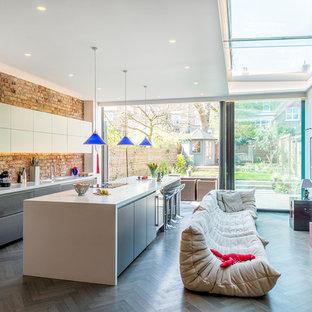 ロンドンの広いコンテンポラリースタイルのおしゃれなキッチン (一体型シンク、フラットパネル扉のキャビネット、グレーのキャビネット、人工大理石カウンター、ピンクのキッチンパネル、レンガのキッチンパネル、シルバーの調理設備、濃色無垢フローリング、グレーの床) の写真