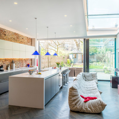 Example of a large trendy single-wall dark wood floor and gray floor open concept kitchen design in London with an integrated sink, flat-panel cabinets, gray cabinets, solid surface countertops, pink backsplash, brick backsplash, stainless steel appliances and an island