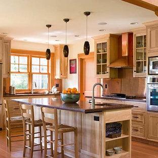 Große Klassische Wohnküche in L-Form mit Einbauwaschbecken, Glasfronten, hellen Holzschränken, Kupfer-Arbeitsplatte, Küchenrückwand in Metallic, Rückwand aus Metallfliesen, Küchengeräten aus Edelstahl, braunem Holzboden, Kücheninsel, braunem Boden und brauner Arbeitsplatte in Portland