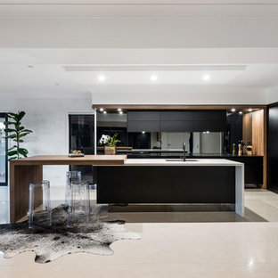 Contemporary l-shaped eat-in kitchen in Gold Coast - Tweed with an undermount sink, flat-panel cabinets, black cabinets, wood benchtops, metallic splashback, mirror splashback, black appliances, with island and beige floor.