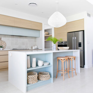 Inspiration for a mid-sized beach style galley open plan kitchen in Gold Coast - Tweed with an undermount sink, flat-panel cabinets, light wood cabinets, quartz benchtops, beige splashback, ceramic splashback, stainless steel appliances, ceramic floors, with island, white floor and white benchtop.