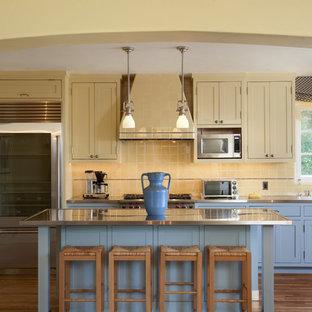 Idéer för medelhavsstil kök, med skåp i shakerstil, gula skåp, bänkskiva i rostfritt stål, gult stänkskydd, rostfria vitvaror, mörkt trägolv och en köksö