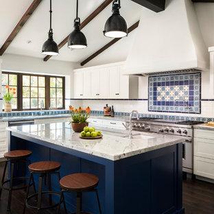 Idéer för ett mellanstort medelhavsstil vit kök, med en undermonterad diskho, luckor med infälld panel, vita skåp, bänkskiva i kvarts, flerfärgad stänkskydd, stänkskydd i terrakottakakel, rostfria vitvaror, mörkt trägolv, en köksö och brunt golv