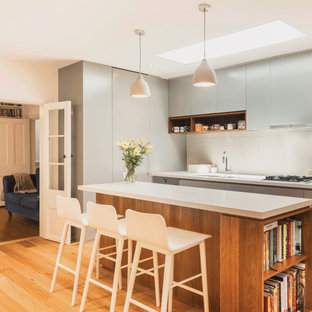 Contemporary kitchen in Sydney with an undermount sink, flat-panel cabinets, grey cabinets, white splashback, mosaic tile splashback, light hardwood floors, with island, beige floor and white benchtop.