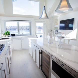 Идея дизайна: большая параллельная кухня в стиле модернизм с обеденным столом, врезной раковиной, плоскими фасадами, белыми фасадами, столешницей из кварцевого композита, белым фартуком, фартуком из стеклянной плитки, техникой из нержавеющей стали, полом из керамогранита, островом, белым полом и белой столешницей