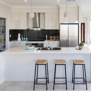 Design ideas for a large contemporary u-shaped eat-in kitchen in Other with a double-bowl sink, flat-panel cabinets, beige cabinets, black splashback, stainless steel appliances, with island and beige floor.