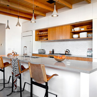 Large contemporary kitchen designs - Example of a large trendy single-wall concrete floor and gray floor kitchen design in Los Angeles with an undermount sink, flat-panel cabinets, white cabinets, white backsplash, subway tile backsplash, white appliances, an island and gray countertops