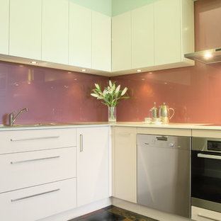 Mid-sized contemporary u-shaped separate kitchen in Sydney with a double-bowl sink, flat-panel cabinets, white cabinets, quartz benchtops, pink splashback, glass sheet splashback, stainless steel appliances and terra-cotta floors.