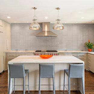 Idéer för ett mellanstort klassiskt u-kök, med en undermonterad diskho, släta luckor, beige skåp, bänkskiva i återvunnet glas, grått stänkskydd, stänkskydd i glaskakel, integrerade vitvaror, mörkt trägolv och en köksö