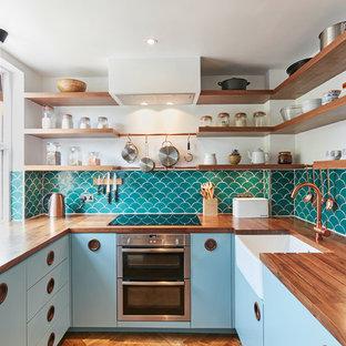 Inspiration för avskilda, små retro u-kök, med en rustik diskho, släta luckor, blå skåp, träbänkskiva, rostfria vitvaror, mellanmörkt trägolv, brunt golv, grönt stänkskydd och stänkskydd i keramik