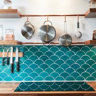 ロンドンの小さいエクレクティックスタイルのおしゃれなキッチン (エプロンフロントシンク、フラットパネル扉のキャビネット、青いキャビネット、木材カウンター、青いキッチンパネル、セメントタイルのキッチンパネル、シルバーの調理設備の、濃色無垢フローリング、アイランドなし、茶色い床) の写真
