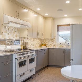 ポートランドの中サイズのミッドセンチュリースタイルのおしゃれなキッチン (アンダーカウンターシンク、フラットパネル扉のキャビネット、マルチカラーのキッチンパネル、セラミックタイルのキッチンパネル、白い調理設備、リノリウムの床、アイランドなし、クオーツストーンカウンター、グレーのキャビネット) の写真