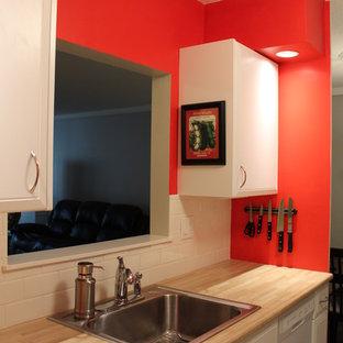 Geschlossene, Zweizeilige, Kleine Moderne Küche ohne Insel mit Einbauwaschbecken, profilierten Schrankfronten, weißen Schränken, Laminat-Arbeitsplatte, Küchenrückwand in Weiß, Rückwand aus Metrofliesen, weißen Elektrogeräten und Vinylboden in Sonstige