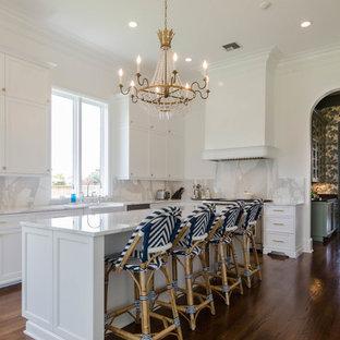 Foto på ett mellanstort maritimt u-kök, med en rustik diskho, luckor med upphöjd panel, vita skåp, marmorbänkskiva, vitt stänkskydd, rostfria vitvaror, mörkt trägolv och en köksö