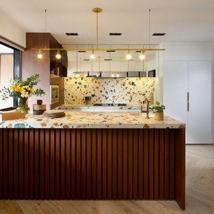 Новые идеи обустройства дома: п-образная кухня в стиле ретро с врезной раковиной, плоскими фасадами, белыми фасадами, столешницей терраццо, разноцветным фартуком, светлым паркетным полом, полуостровом, бежевым полом и разноцветной столешницей