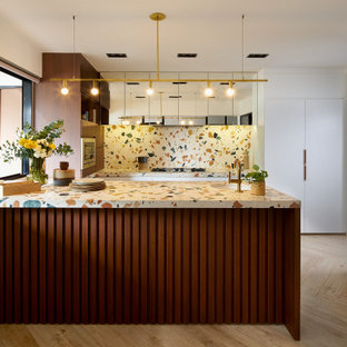 Inspiration for a midcentury u-shaped kitchen in Singapore with an undermount sink, flat-panel cabinets, white cabinets, terrazzo benchtops, multi-coloured splashback, light hardwood floors, a peninsula, beige floor and multi-coloured benchtop.