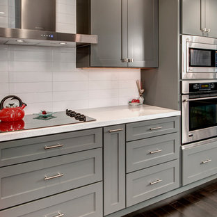 Idéer för ett mellanstort modernt kök, med en undermonterad diskho, skåp i shakerstil, grå skåp, bänkskiva i kvarts, vitt stänkskydd, rostfria vitvaror, mörkt trägolv och en köksö