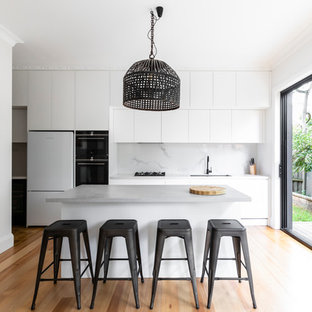 This is an example of a contemporary kitchen in Sydney with an undermount sink, flat-panel cabinets, white cabinets, white splashback, stone slab splashback, white appliances, light hardwood floors, with island, beige floor and white benchtop.