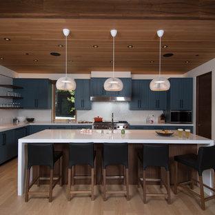 Mid-sized modern u-shaped open plan kitchen in Sacramento with an integrated sink, flat-panel cabinets, blue cabinets, quartz benchtops, white splashback, porcelain splashback, panelled appliances, light hardwood floors, with island, beige floor and white benchtop.
