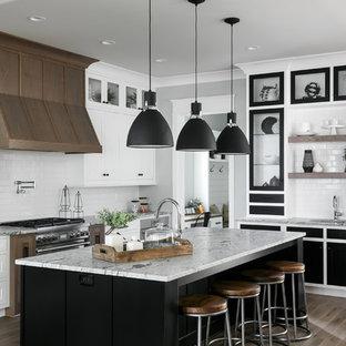Ejemplo de cocina clásica renovada con armarios estilo shaker, puertas de armario blancas, salpicadero blanco, salpicadero de azulejos tipo metro, electrodomésticos de acero inoxidable, suelo de madera oscura, una isla, suelo marrón y encimeras grises