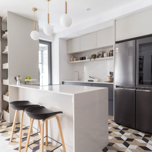 Photo of a contemporary galley kitchen in Singapore with flat-panel cabinets, grey cabinets, black appliances, a peninsula, multi-coloured floor and white benchtop.
