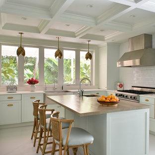 Свежая идея для дизайна: п-образная кухня в морском стиле с фасадами в стиле шейкер, зелеными фасадами, деревянной столешницей, белым фартуком, фартуком из плитки кабанчик, техникой из нержавеющей стали, островом, раковиной в стиле кантри, белым полом и бежевой столешницей - отличное фото интерьера