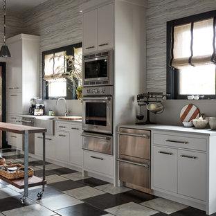 Diseño de cocina de galera, actual, con salpicadero verde, dos o más islas, fregadero sobremueble, armarios con paneles lisos, puertas de armario blancas, electrodomésticos de acero inoxidable y suelo multicolor