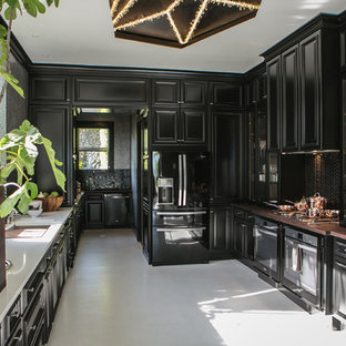 Photo of a large modern galley separate kitchen in San Francisco with a double-bowl sink, louvered cabinets, black cabinets, quartzite benchtops, metallic splashback, ceramic splashback, black appliances and slate floors.