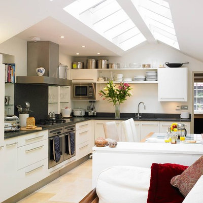 Open concept kitchen - contemporary l-shaped open concept kitchen idea in London with stainless steel appliances and white cabinets