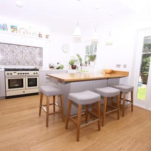 他の地域の大きいヴィクトリアン調のおしゃれなキッチン (ドロップインシンク、シェーカースタイル扉のキャビネット、グレーのキャビネット、大理石カウンター、白いキッチンパネル、カラー調理設備、淡色無垢フローリング、茶色い床、白いキッチンカウンター) の写真