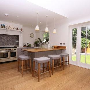 他の地域の広いヴィクトリアン調のおしゃれなキッチン (ドロップインシンク、シェーカースタイル扉のキャビネット、グレーのキャビネット、大理石カウンター、白いキッチンパネル、カラー調理設備、淡色無垢フローリング、茶色い床、白いキッチンカウンター) の写真