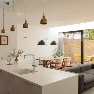 Esempio di una cucina minimal con lavello integrato, ante lisce e penisola