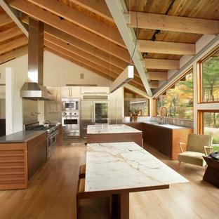 Idéer för mycket stora funkis kök, med släta luckor, skåp i mellenmörkt trä, marmorbänkskiva, flera köksöar, en undermonterad diskho, stänkskydd med metallisk yta, stänkskydd i metallkakel, rostfria vitvaror och ljust trägolv
