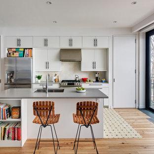 ニューヨークのエクレクティックスタイルのおしゃれなキッチン (アンダーカウンターシンク、フラットパネル扉のキャビネット、白いキャビネット、クオーツストーンカウンター、黄色いキッチンパネル、セメントタイルのキッチンパネル、シルバーの調理設備、セメントタイルの床、黄色い床、グレーのキッチンカウンター) の写真