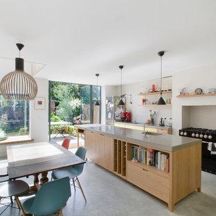 Zweizeilige Moderne Wohnküche mit Betonboden, offenen Schränken, gelben Schränken, schwarzen Elektrogeräten und Kücheninsel in London