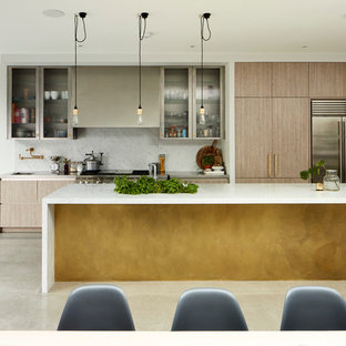 Photo of a contemporary galley kitchen in London with flat-panel cabinets, medium wood cabinets, white splashback, stainless steel appliances, concrete flooring and an island.
